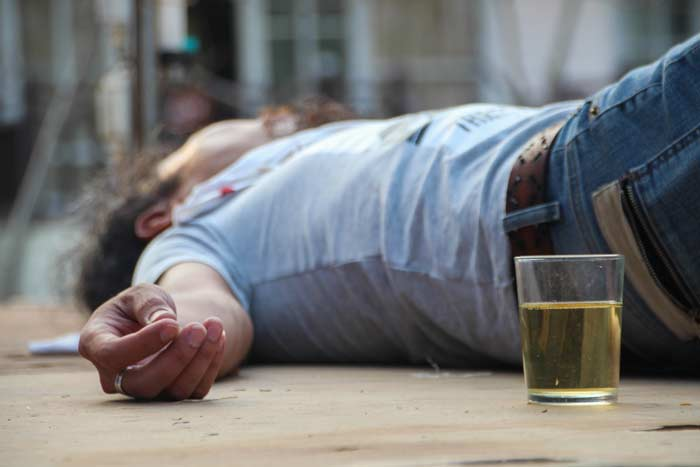 Man passed out by alcoholic drink